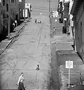 Boys sidewalk sledding on steep San Francisco hill street, 1952