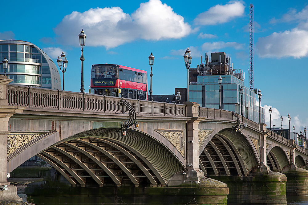 A red London bus crossing Battersea Bridge in West London. Battersea Bridge is a five-span arch bridge with cast-iron girders and granite piers crossing the River Thames in London, England. It is situated on a sharp bend in the river, and links Battersea south of the river with Chelsea to the north.