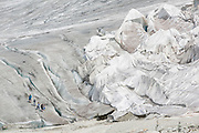 Tourists walk along the edge of the Rhone Glacier in Switzerland. To the left of them can be seen huge sheets of fleece blankets used to cover an ice tunnel. The Rhone Glacier now melts more than 70 centimeters in thickness every week in the summer months. Between 1996 and 2006, an estimated 0.9 billion cubic metres of water melted yearly from the Swiss glaciers. That number is likely much higher today. Switzerland just had the hottest July since 1864, it has the lowest rainfall since 1921, and the rivers are running at record low levels. The covering of the glacier is the idea of Philipp Carlen, who owns and operates an ice cave at the mouth of the glacier. The glacier is still melting, but by covering it with blankets, he is able to attract tourists who are coming to see the dying glacier.