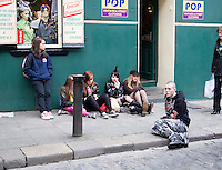 Young people sitting on the pavement outside a vintage clothes shop in Temple Bar Dublin Ireland.