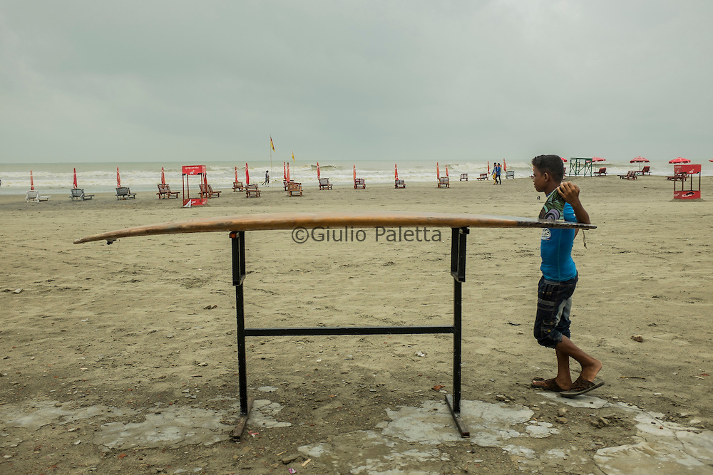 A young boy wait for the right moment to surf while waiting on Cox's Bazar's beach, Bangladesh