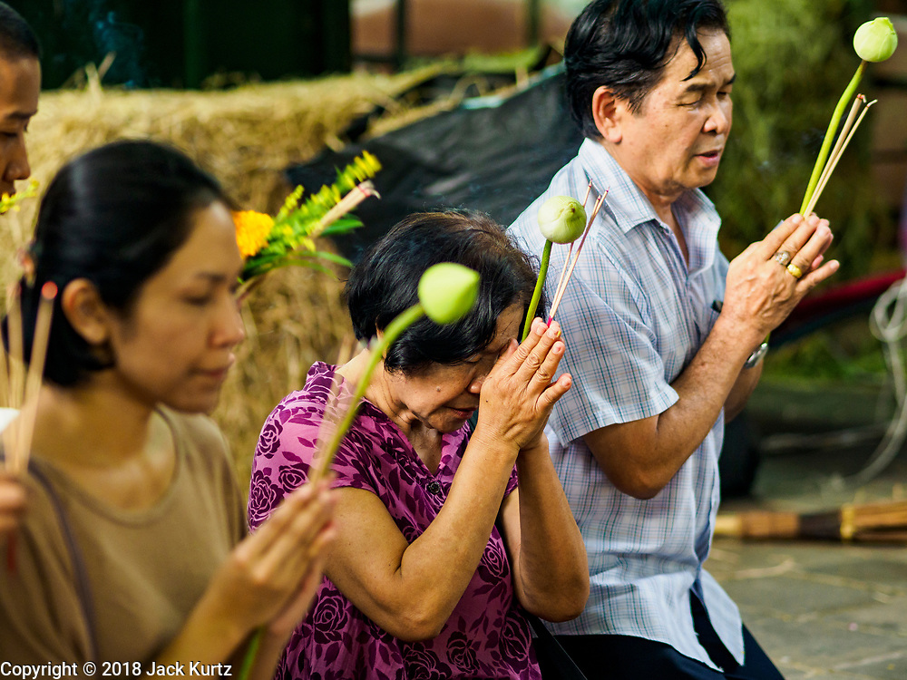 29 MAY 2018 - BANGKOK, THAILAND:People hold lotus blossoms while they pray during Vesak observances at Wat Hua Lamphong in Bangkok. Vesak is the Buddha's birthday, and one of the most important holy days in the Theravada Buddhist religion. Many Thais visit their local temples for Vesak and rededicate themselves to the Dharma, listen to talks about Buddhism and make merit by bringing flowers to the temple.    PHOTO BY JACK KURTZ