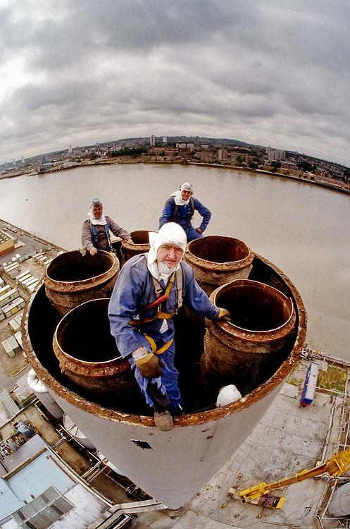 Steeple jacks taking down a chimney in Silver Town, East London.