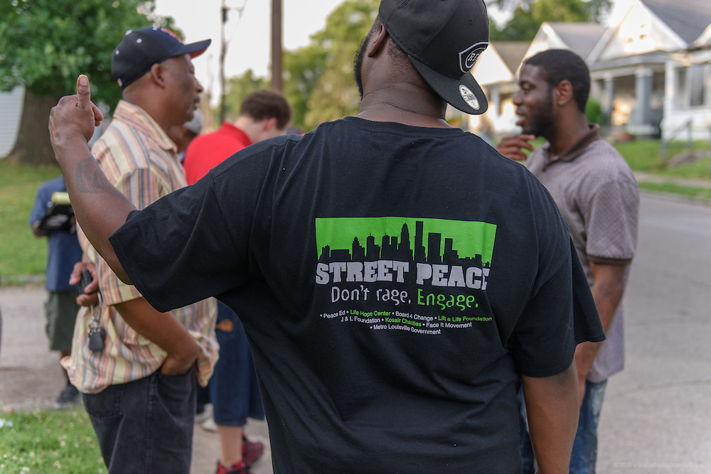 "WE NEED APPROVAL TO USE THIS ONE --- A Street Team Leader wears a Street Peace T-shirt that says, ""Don't Rage, Engage."" (Photo by Brian Bohannon)"