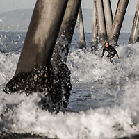 A young surfer rides under the pier at Huntington Beach, CA.