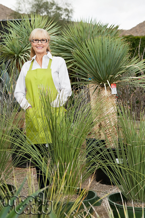 Portrait of a senior female gardener surrounded by potted plants