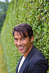 PhotoLibrary-14 portrait of an Asian American man in a sports jacket  near a hedge in The Hamptons
