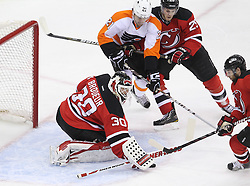 May 3, 2012; Newark, NJ, USA;  New Jersey Devils goalie Martin Brodeur (30) makes a save while Philadelphia Flyers left wing James van Riemsdyk (21) and New Jersey Devils defenseman Mark Fayne (29) battle for the rebound during the first period in game three of the 2012 Eastern Conference semifinals at the Prudential Center.