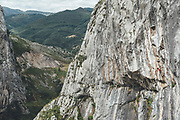 Rock climber male climbing on overhanging limestone mountain Mamut climbing athlete Bobbi Bensman enjoying a climbing trip at Roca Verde, Asturias, Spain