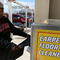 Alicia King runs her carmats through the cleaner Saturday while washing her vehicle