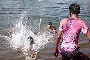 A boy is thrown into Lake Pichola as people take a bathe after the festival of Holi, in Udaipur, Rajasthan, India