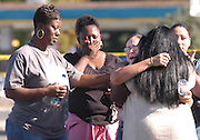 The mother of Elric Wheeler's 3 week old baby Trevhon Wheeler, Shahanna Wheeler, 21, is comforted by family members and friends as she arrives on the scene of the killing of Elric Wheeler, 24, of Fremont, at the Meadowsquare Shopping Center in Fremont, Ca. Tues. Oct 23, 2007. Wheeler got shot in the back after an altercation of two groups of males outside a liquor store, and he fell to the ground at the Maple Leaf Donuts store where he was pronounced dead by paramedics.