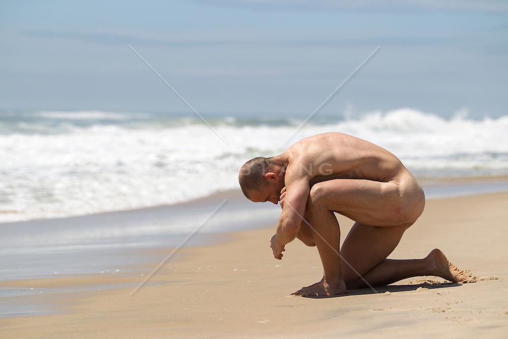 nude man kneeling down at the beach
