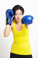 Portrait of young Asian woman wearing boxing gloves against white background