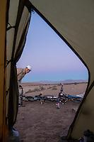 Cyclist looking into his tent, Atacama, Chile