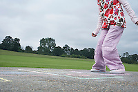 Girl (7-9) playing hop-scotch in school playground low section