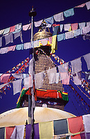 Brightly coloured prayer flags stretch across the sky in front of the Bodnath Stupa in the Kathmandu Valley.