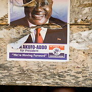 A girl looks through a hole in a wall plastered with a poster promoting New Patriotic Party (NPP) candidate Nana Akufo-Addo ahead of the presidential election in Afiaso, Ghana on Monday August 25, 2008.