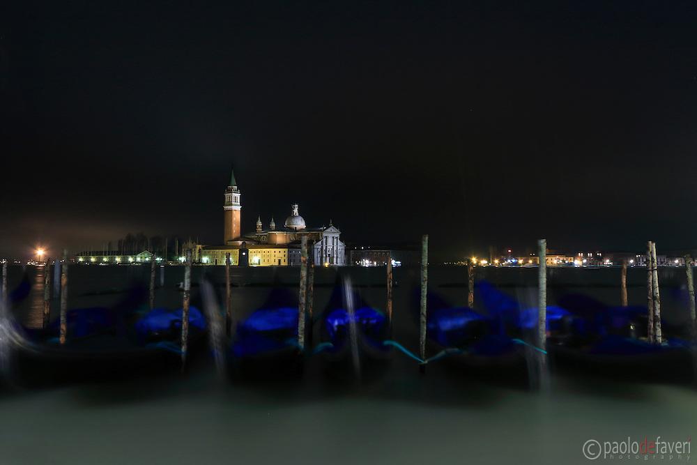 Swinging gondolas at Riva degli Schiavoni in Venice by night, with the basilica of San Giorgio Maggiore in the background