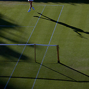 'Slam the Light'<br /> <br /> The summer light of the four tennis grand slams in Australia, France, England and USA provide an amazing contrast of light and condition, each tournament providing a uniqueness and beauty.<br />  From the harsh Australian summer light of Melbourne, to the spring light reflecting off the clay courts of Roland Garros in Paris, the low and late setting northern summer light casting beautiful long shadows on the lush Wimbledon grass in London and the early autumn soft subtle light of Flushing Meadows in New York.<br /> <br /> <br /> Svetlana Kuznetsova, Russia, in action against Akiko Morigami, Japan in the late eveing light  during the first round match at the All England Lawn Tennis Championships at Wimbledon, London, England on Tuesday, June 23, 2009. Photo Tim Clayton..