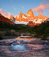On a rare cloudless morning majestic Monte Fitz Roy, in Argentina's Los Glaciares National park, illuminated in the first light of day, towers over a small, peaceful mountain stream.