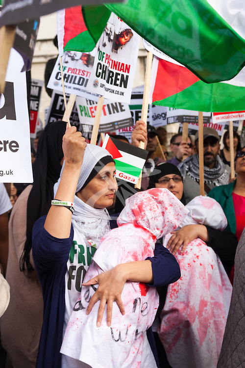 """London, August 23rd 2014. Women display """"dead babies"""" symbolising the many children killed since Israel's Operation Protective Edge began, as hundreds of pro- Palestine protesters demonstrate outside Downing Street demanding that Britain stops arming Israel."""