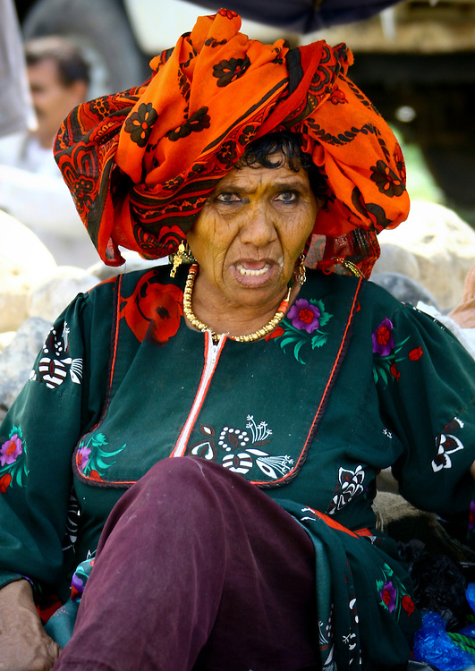 Yemen, Taiz, Jebel Saber, old woman with orange scarf and jewels. Women of Jebel Saber wear very special jewels. They are characteristically outgoing, shouting and even playfully challenging men.