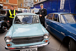 © licensed to London News Pictures. London, UK 26/02/2014. Metropolitan Police Commissioner Sir Bernard Hogan-Howe posing with veteran police cars outside New Scotland Yard as the Met's iconic cop cars dating back to 1948 taking part at a convoy through central London. Vehicles including the 1948 Wolseley, 1970 Morris, Minor 1000 and the 1973 Special Branch Rover P6 leaving Hampton Traffic Garage for the final time to head up to the Met's Peel Centre in Hendon which will be the new home of the fleet. Photo credit: Tolga Akmen/LNP
