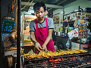 "17 JANUARY 2016 - BANGKOK, THAILAND: A food stall vendor grills chicken ""satae,"" a marinted grilled meat on stick served with peanut sauce, on Sukhumvit Soi 38, one of the most famous street food areas in Bangkok. The food carts and small restaurants along the street have been popular with tourists and Thais alike for more than 40 years. The family that owns the land along the soi recently decided to sell to a condominium developer and not renew the restaurant owners' leases. More than 40 restaurants and food carts will have to close. Most of the restaurants on the street closed during the summer of 2015. The remaining restaurants are supposed to close by the end of this week.          PHOTO BY JACK KURTZ"