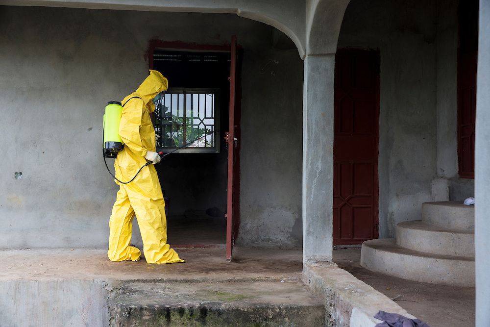 Ambulance being dispatched to westren area of Freetown, Sierra Leone to attend a suspected case of ebola. The cleaner disinfects the house of the susptected case with chlorinated water. Photo by UNMEER/Martine Perret. 15 December 2014