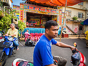 """18 AUGUST 2014 - BANGKOK, THAILAND: A man rides his scooter past the stage for the Lehigh Leng Kaitoung Opera troupe which performed at Chaomae Thapthim Shrine, a small Chinese shrine in a working class neighborhood of Bangkok. The performance was for Ghost Month. Chinese opera was once very popular in Thailand, where it is called """"Ngiew."""" It is usually performed in the Teochew language. Millions of Chinese emigrated to Thailand (then Siam) in the 18th and 19th centuries and brought their culture with them. Recently the popularity of ngiew has faded as people turn to performances of opera on DVD or movies. There are still as many 30 Chinese opera troupes left in Bangkok and its environs. They are especially busy during Chinese New Year and Chinese holiday when they travel from Chinese temple to Chinese temple performing on stages they put up in streets near the temple, sometimes sleeping on hammocks they sling under their stage. Most of the Chinese operas from Bangkok travel to Malaysia for Ghost Month, leaving just a few to perform in Bangkok.     PHOTO BY JACK KURTZ"""