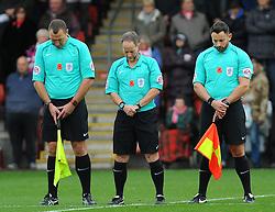 Referee Robert Lewis and his assistants stand for a minutes silence -Mandatory by-line: Nizaam Jones/JMP - 11/11/2017 - FOOTBALL - LCI Rail Stadium - Cheltenham, England - Cheltenham Town v Luton Town - Sky Bet League Two