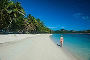 Woman walking on a a white sand beach, Nanuya Lailai island, the blue lagoon, Yasawas, Fiji, South Pacific, MR