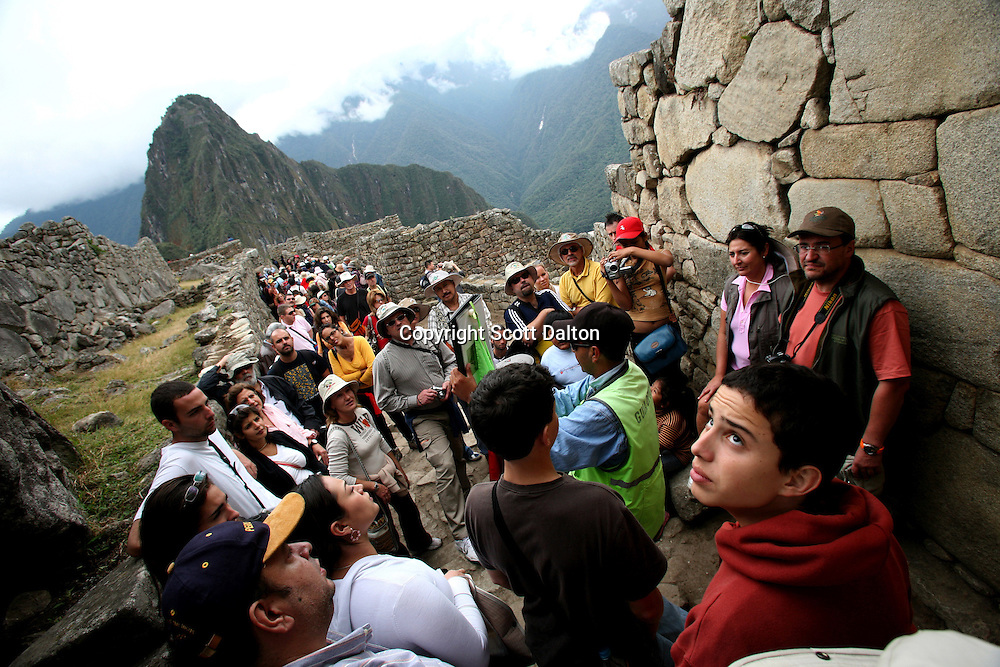 Tourists listen to a guide at the lost Inca city of Machu Picchu in Peru, on August 11, 2007. Machu Picchu was recently voted one of the new Seven Wonders of the World. Some experts are concerned if the site can maintain the large number of tourists that visit the site and are worried that if proposals to increase the number of visitors will have adverse effects on the ancient ruins. (Photo/Scott Dalton)
