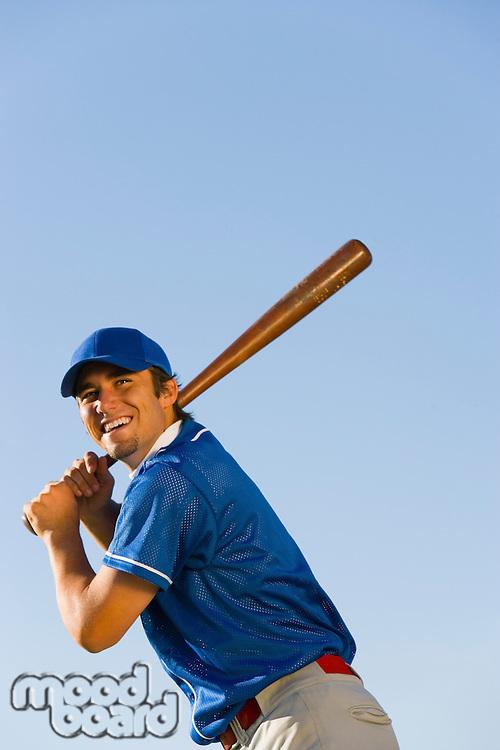 Baseball player swinging baseball bat (low angle view)