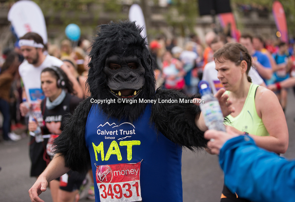 An athlete dressed as a gorilla takes a drink at the Temple tube Buxton drinks station. The Virgin Money London Marathon, Sunday 26th April 2015.<br /> <br /> Photo: Jed Leicester for Virgin Money London Marathon<br /> <br /> For more information please contact Penny Dain at pennyd@london-marathon.co.uk