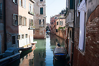 view of a channel in Venice, Italy. laundries on the houses walls, boats on channel and historical buildings.