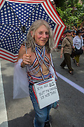 "An octogenarian woman bedecked in rded, white, nd blue marches with a sign which reads ""I'm age 82 but my parade is not thru."""