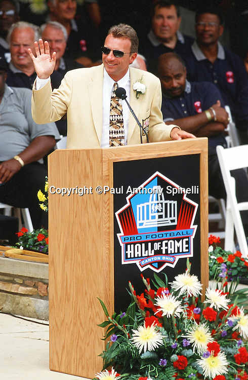 Former Former San Francisco 49ers quarterback Joe Montana waves as he speaks at the podium during the NFL Pro Football Hall of Fame Induction Ceremony on July 29, 2000 in Canton, Ohio. (©Paul Anthony Spinelli)