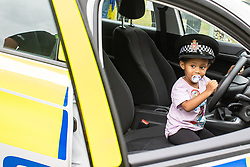© Licensed to London News Pictures . 12/08/2018. Manchester , UK . NYLAH RICHINGS (three, from Radcliffe) in a police car , at the event . The second day of the annual Caribbean Carnival in Alexandra Park in Moss Side , celebrating music , food and Afro-Caribbean culture . A nearby shooting overnight lead to at least ten people injured . Ten people are in hospital . Photo credit : Joel Goodman/LNP