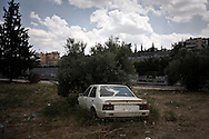 Greece, Athens, July 2013 - A car has been left in a field at Metamorfosi, a north suburb of Athens. Over 100.000 car plates were deposited in all tax offices in Greece within the last month of 2012 since their owners can not afford the high taxes.