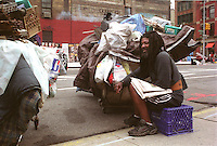 homeless man with all his belongings walking the streets during the day New York City USA.