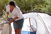 """Jennifer White packs her camping gear into a waterproof """"Drybag"""" during a river trip on the Colorado River in Westwater Canyon, Utah."""
