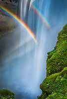 close up detail featuring a rainbow in Skogafoss waterfall in sourthern Iceland