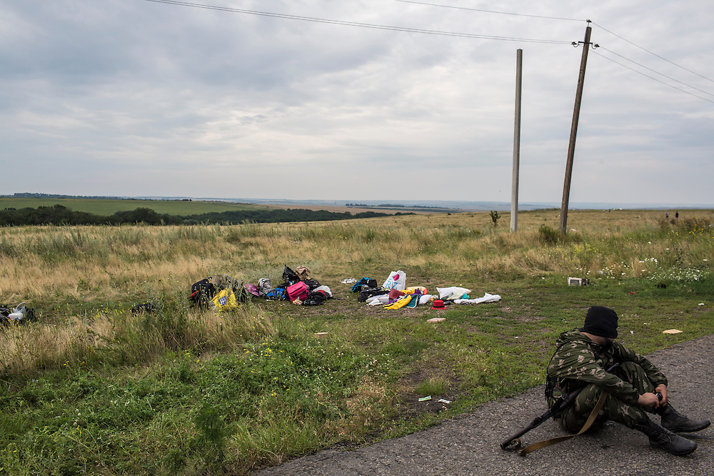 GRABOVO, UKRAINE - JULY 19: A pro-Russia separatist fighter near personal belongings of passengers at the scene of the crash of Malaysia Airlines flight MH 17 after separatists established control of the site on July 19, 2014 in Grabovo, Ukraine. Malaysia Airlines flight MH17 was travelling from Amsterdam to Kuala Lumpur when it crashed killing all 298 on board including 80 children. The aircraft was allegedly shot down by a missile and investigations continue over the perpetrators of the attack. (Photo by Brendan Hoffman/Getty Images) *** Local Caption ***