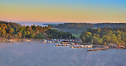 Panoramic view of boats moored amid the islands of the Stockholm Archipelago at dawn on a foggy morning seen from the Baltic Sea with stone pier swans and cygnets at right