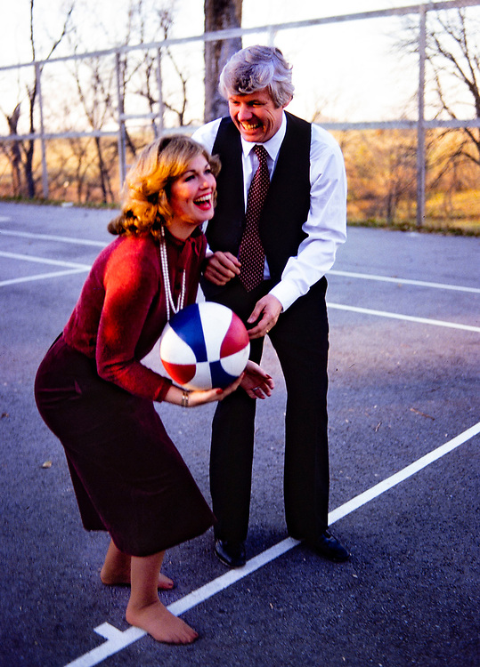 "Phyllis George and new husband, Kentucky governor elect John Y Brown play a game of ""horse"" on a basketball court at their home in Lexington. Brown is trying to distract his new bride by kissing and blowing in her ear. Phyllis Ann George was an American businesswoman, actress, and sportscaster. She was also Miss Texas 1970, Miss America 1971, and the First Lady of Kentucky from 1979 to 1983. Ms. George died, aged 70, of complications from Polycythemia vera on May 14, 2020 in Lexington, Kentucky."