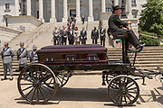 The horse-drawn caisson carrying the casket of slain State Senator Clementa Pinckney arrives at the State House for the last time as Governor Nikki Haley waits to receive it June 24, 2015 in Columbia, South Carolina. Pinckney is one of the nine people killed in last weeks Charleston church massacre.