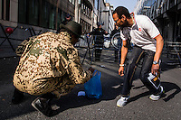 Brussels April 9 2015. A group of Congolese protesters in Brussels gathered in front of the RDC Congolese embassy. they asked for attention of the killed students in the university of Kenya and were angry all attention went to the Charlie Hebdo attacks and not to this terrorist attack. a massgrave found in maluku, next to kinshasha was another reason to protest against Kabila.After the protest Congolese men clean up the candles they had lit in front of the police and embassy