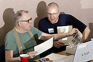 Lt. Bob Shadowens (right) looks on as Alan Routt scans photos at a reunion of Fairborn fire fighters at the Fire Administration offices, Friday, April 11, 2008.  Shadowens is set to retire this summer.
